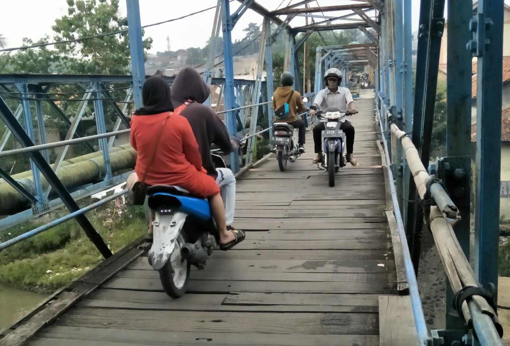 Pengendara motor melintasi jembatan yang menghubungkan Kelurahan Gunung Batu dan Kebon Kelapa.