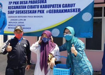 istri Kepala Desa Padasuka, Sholahal Gina Ghunawan, S.Pd, membagikan masker kepada warga yang sedang beraktivitas di luar rumah.
